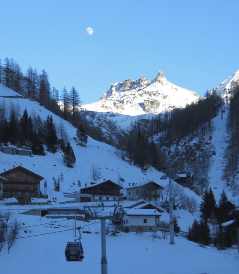 A gondola carries skiers back to Algana from Gressoney and past small hotels,