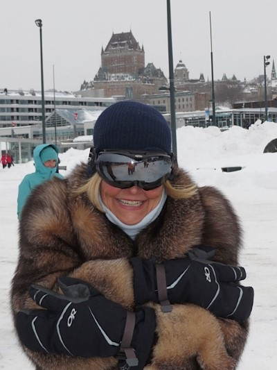 Dressed for the Quebec cold with Chateau Frontenac towering above the city, this tourist enjoys a day in Quebec City