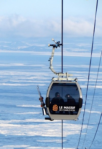 LeMassif Ski Resort Gondola carries skies towards the summit with the frozen St Lawrence River setting the backdrop. The river is 7 miles wide at LeMassif to the south shore in background.