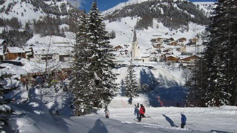 Skiers descend into a mountain village on the Sella Ronda tour as a local church and alpine homes form the setting in the Dolomites