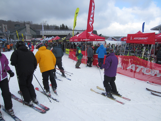 Ski testers leave the base area after selecting new skis and snowboards for a test run.