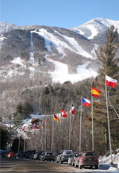Entrance Road to Whiteface Mt Resort displaying International Flag with Mountain serving as backdrop.