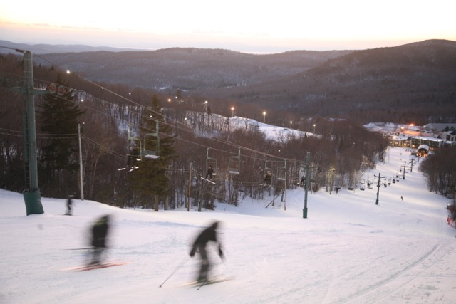 Skiers ride the Bolton Valley double during dusk