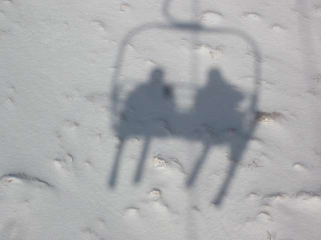 Skiers cast a shadow on the snow as they ride the triple chairlift at Magic Mt.