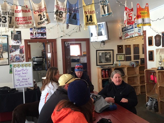 Barbara Cochran enjoys talking with fellow skiers inside the Cochran Ski Area Base lodge. Racing bibs from around the world worn by family racers add to the background.
